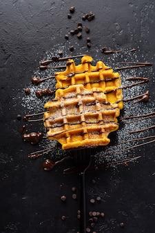 Pumpkin waffles with chocolate and sugar powder on dark old