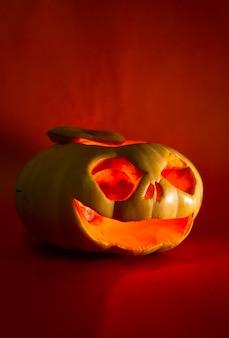 Тыква с резным лицом на хэллоуин на красном фоне
