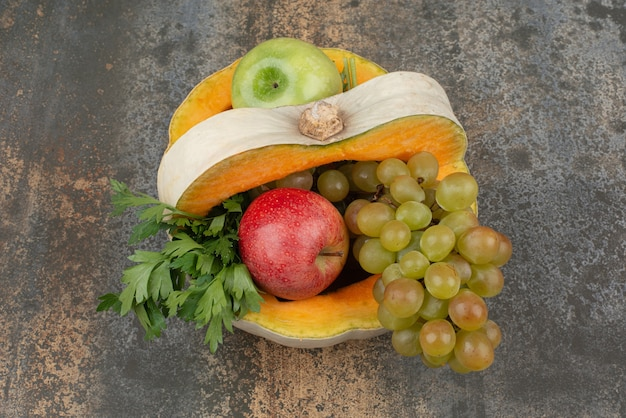 Pumpkin with apples and grapes on marble surface.