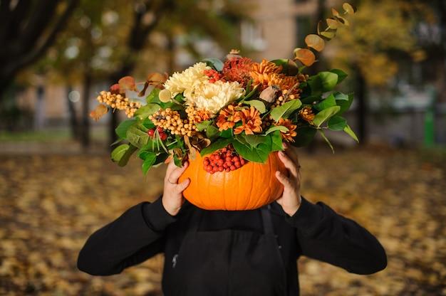 Pumpkin with beautiful bouquet of autumn flowers in florist hands