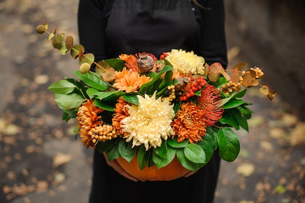 Pumpkin with beautiful bouquet of flowers in woman hands