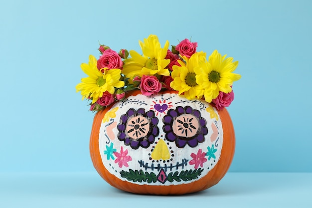 Pumpkin with catrina skull makeup and flowers on blue wall
