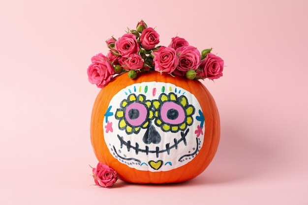 Pumpkin with catrina skull makeup and flowers on pink