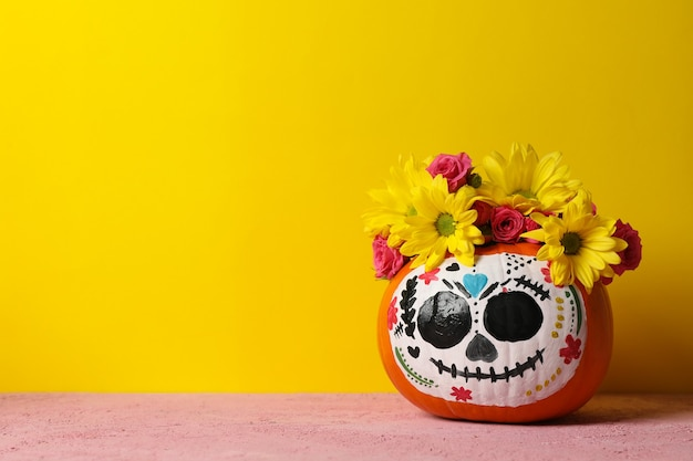Pumpkin with catrina skull makeup and flowers on yellow background