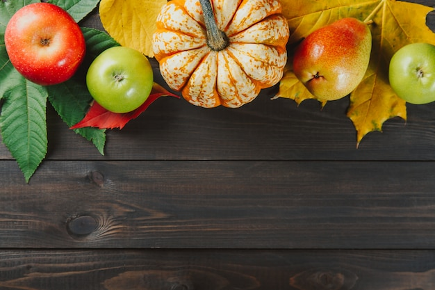 Pumpkin with colorful maple leaves, ripe apples and pear on dark wooden  background