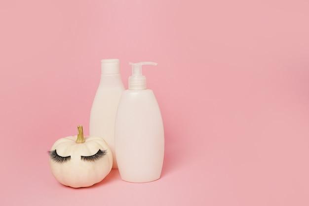 인조 속눈썹이 있는 호박과 분홍색 배경의 화장품 용기 샴푸 또는 젤, 가을 컨셉의 천연 피부 관리