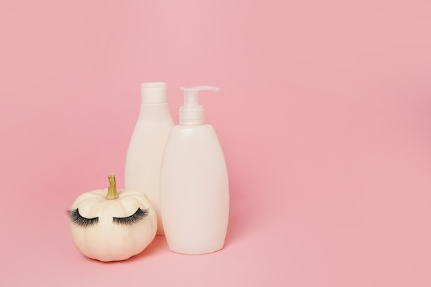 Pumpkin with false eyelashes and mock up cosmetic containers shampoo or gel on pink background, natural skin care in autumn concept