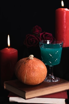 Pumpkin with green drink and books