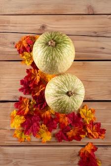 Тыква с листьями на деревянном столе, вид сверху