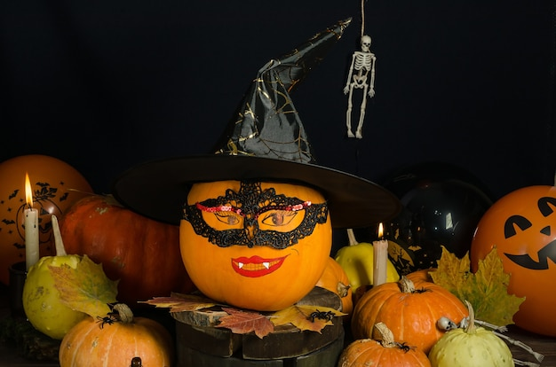 Тыква с раскрашенным лицом в маске и шляпе ведьмы со свечами и другими тыквами