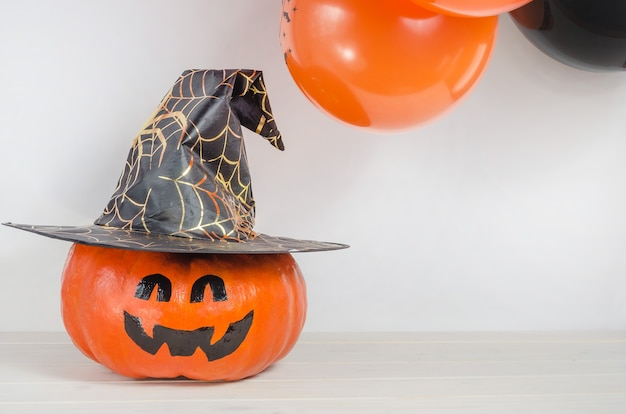 Pumpkin with painted face in witch hat near orange and black balloons