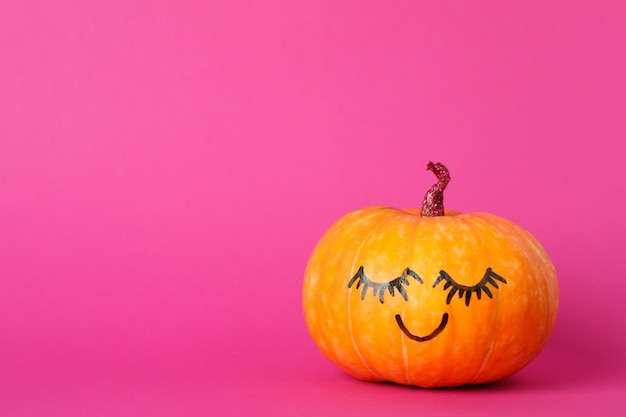 Pumpkin with smile on pink, space for text