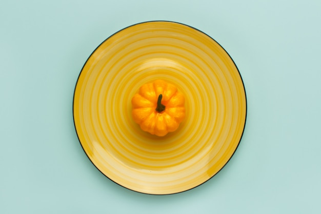 Pumpkin on a yellow dish on pastel turquoise.