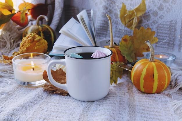 カボチャ一杯のコーヒー秋は燃えるろうそくと開いた本の感謝祭を残します