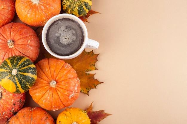 Тыквы и осенние листья, кофейная кружка на бежевом фоне, вид сверху, для текста