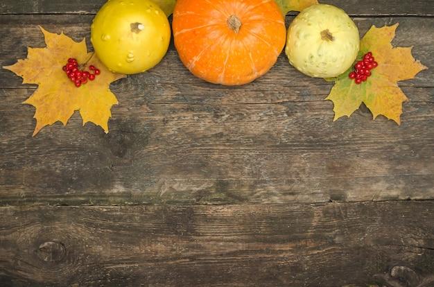 Тыквы и осенние листья на старой деревянной поверхности
