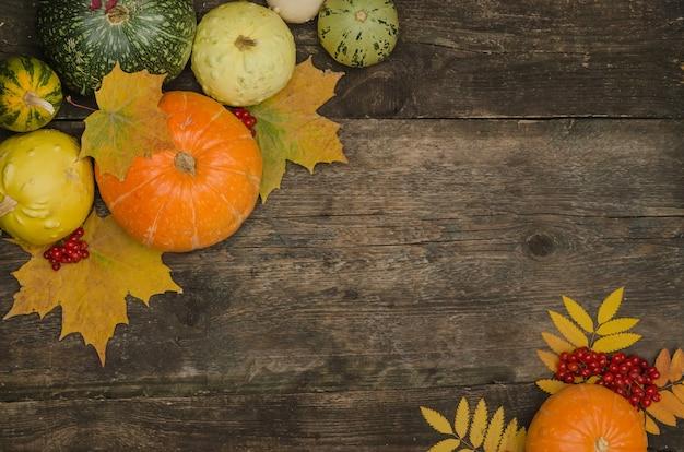 Тыквы и осенние листья на старом деревянном столе