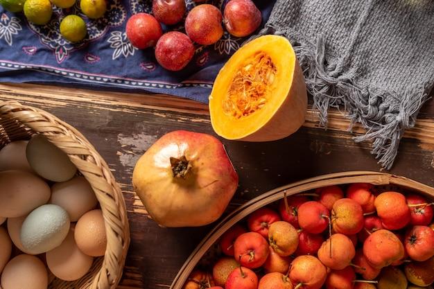 Тыквы и многие другие цвета и разновидности фруктов и овощей на столе с текстурой дерева.