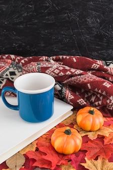 毛布の近くにカボチャとマグカップ