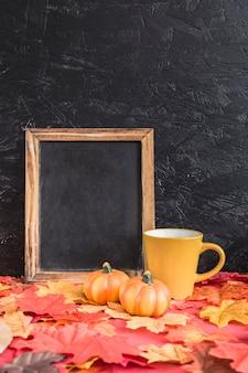 葉の上の黒板の近くにカボチャとマグカップ