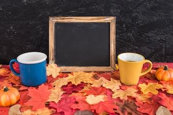 Pumpkins and mugs near blackboard on leaves