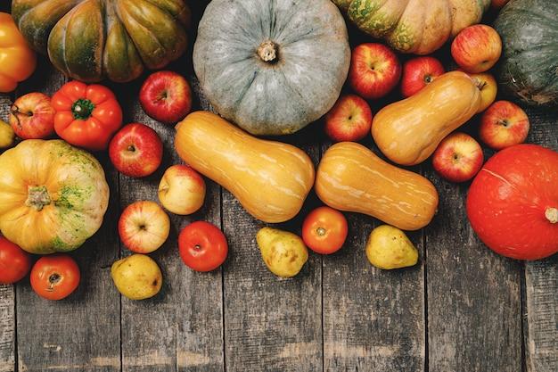 Тыквы и красные яблоки на деревянных фоне гранж
