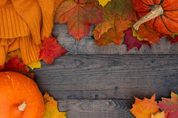 カボチャ、秋のカエデの葉、木製のテーブル、上面図の居心地の良い編みオレンジ色のセーター。