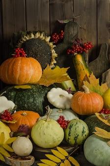 Тыквы, ягоды и осенние листья на старом деревянном столе
