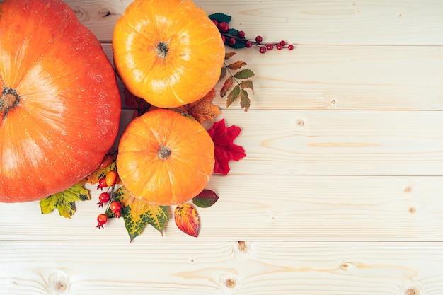 Ягоды тыквы и опавшие листья на деревянном столе