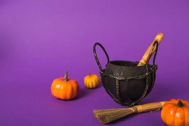 Pumpkins and brooms near cauldron