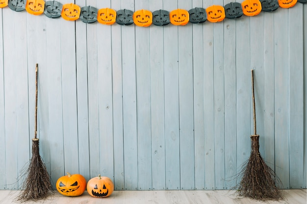 Pumpkins and brooms near the wall with halloween decoration