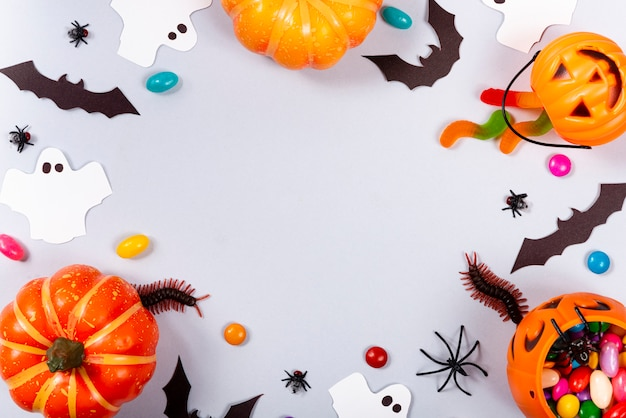 Pumpkins, candies, ghost, spiders, bats and centipede on gray.