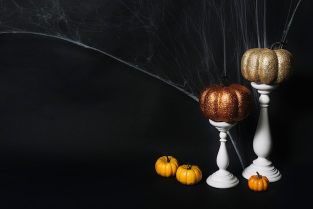 Pumpkins and candles near web