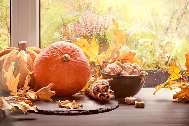 Pumpkins, cinnamon, sugar and leaves by the window