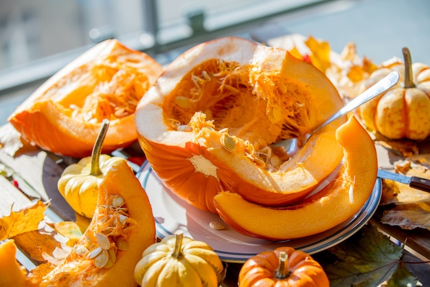 Pumpkins and cut pieces on plate on wooden table