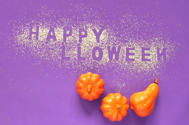 Pumpkins and glitter letters happy halloween on violet background