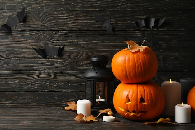 Pumpkins and halloween accessories on wooden background