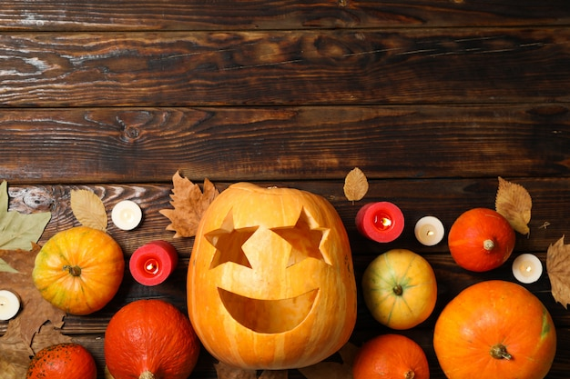 Pumpkins, leaves and candies on wooden table, copy space