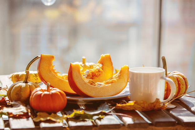 Pumpkins and leaves near cup on a wooden table