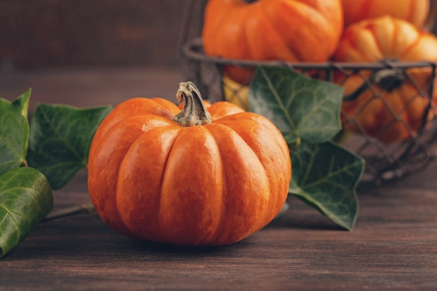 Pumpkins and leaves over wooden background with copy space