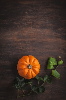 Pumpkins and leaves over wooden copy space.