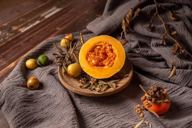 Pumpkins and many other colors and varieties of fruits and vegetables are on the wood grain table
