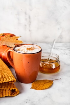 Pumpkins spice latte or coffee with creamy foam in orange cup with pumpkin, leaves, jar of honey and white cozy sweater on white marble background. close up. copy space