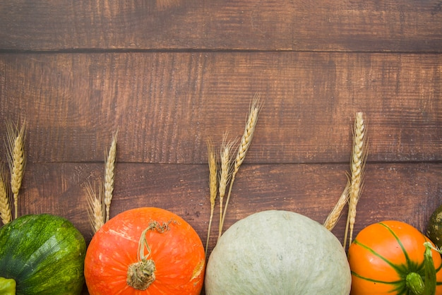 Pumpkins on table with wheat