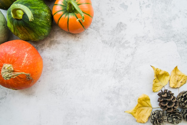 Pumpkins on table with yellow leaflets