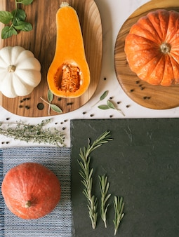 Pumpkins of various colors and shapes on various boards and textile and a slate board