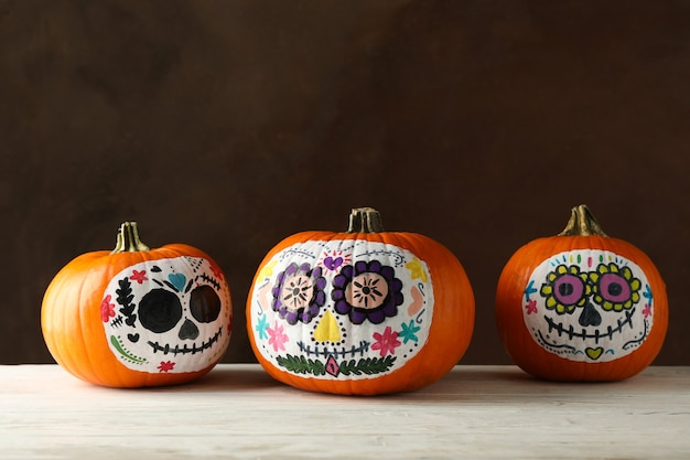 Pumpkins with catrina skull makeup on brown background