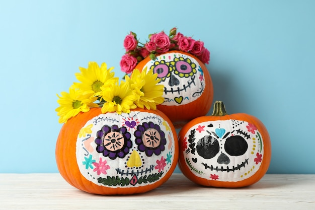 Pumpkins with catrina skull makeup and flowers on blue wall