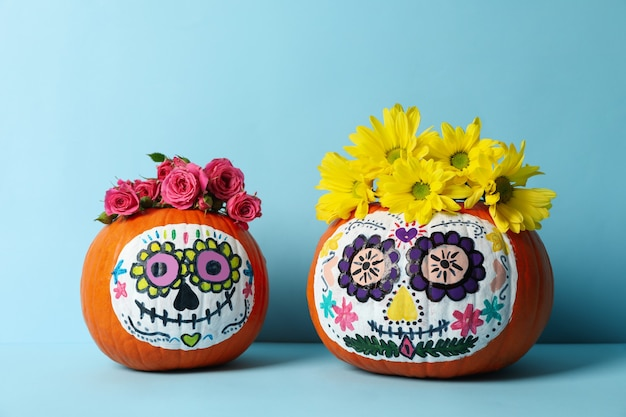 Pumpkins with catrina skull makeup and flowers on blue