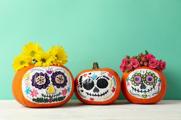 Pumpkins with catrina skull makeup and flowers on mint